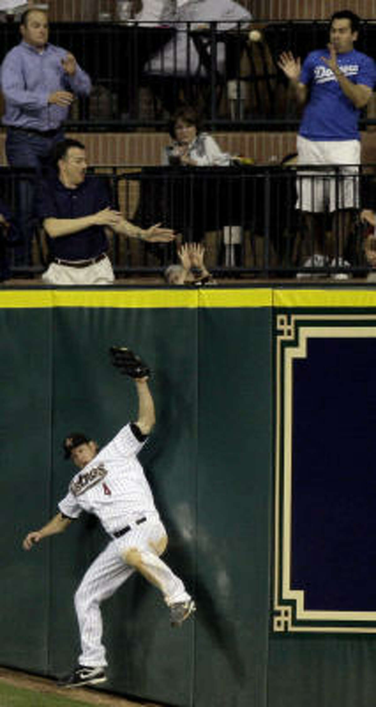 Astros center fielder Jason Michaels (4) hits the wall as fans reach for a two-run home run hit by Los Angeles Dodgers' Manny Ramirez during the seventh inning. Ramirez and Orlando Hudson scored on the homer.