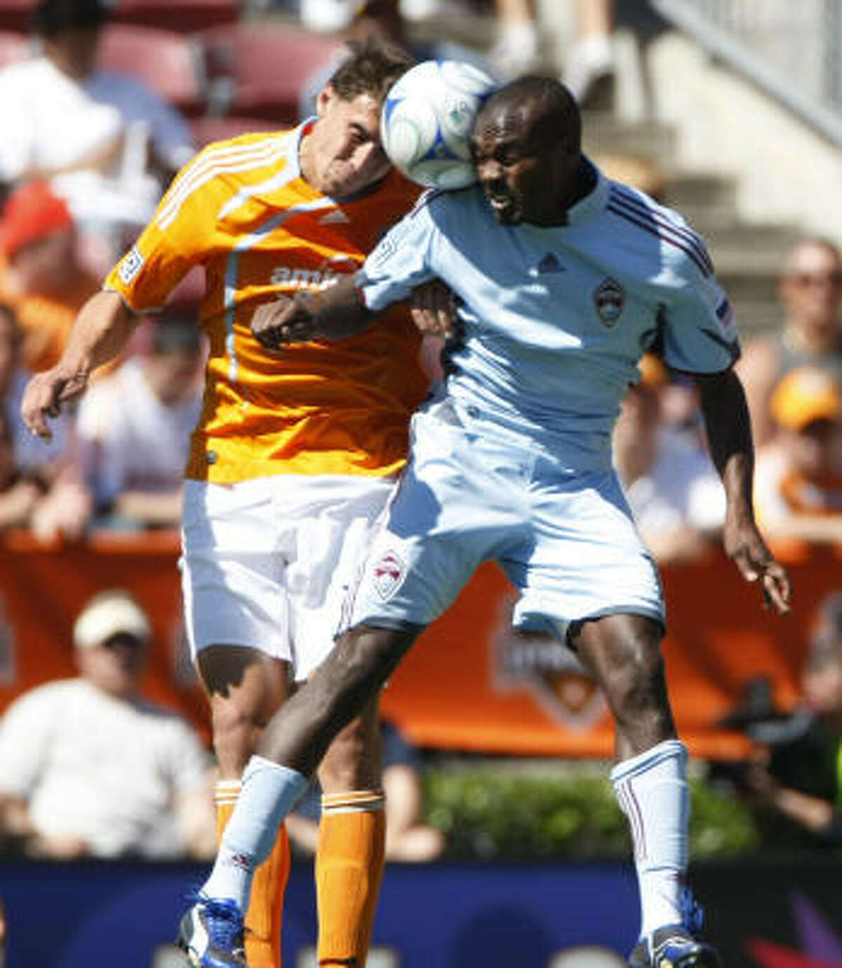 Houston Dynamo defender Geoff Cameron, left, and Colorado Rapids forward Omar Cummings battle for the ball in mid air during a game between the Houston Dynamo and the Colorado Rapids.