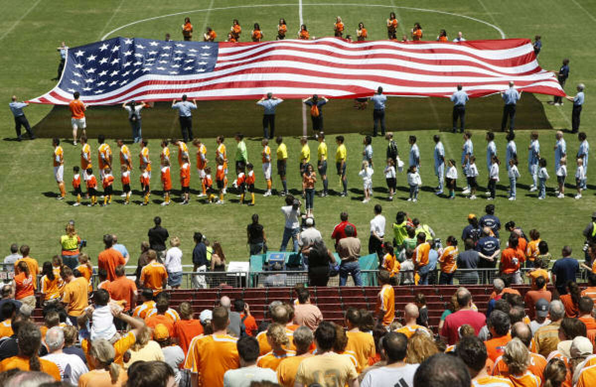 Houston Fire Department officials are seen as they hold on to a large U.S. flag as the Houston Dynamo paused for a moment of silence to remember HFD Captain James Harlow and Fire Fighter Damion Hobs, both from HFD Station 26 who died a week when answering to a fire, before the start of a game between the Houston Dynamo and the Colorado Rapids.