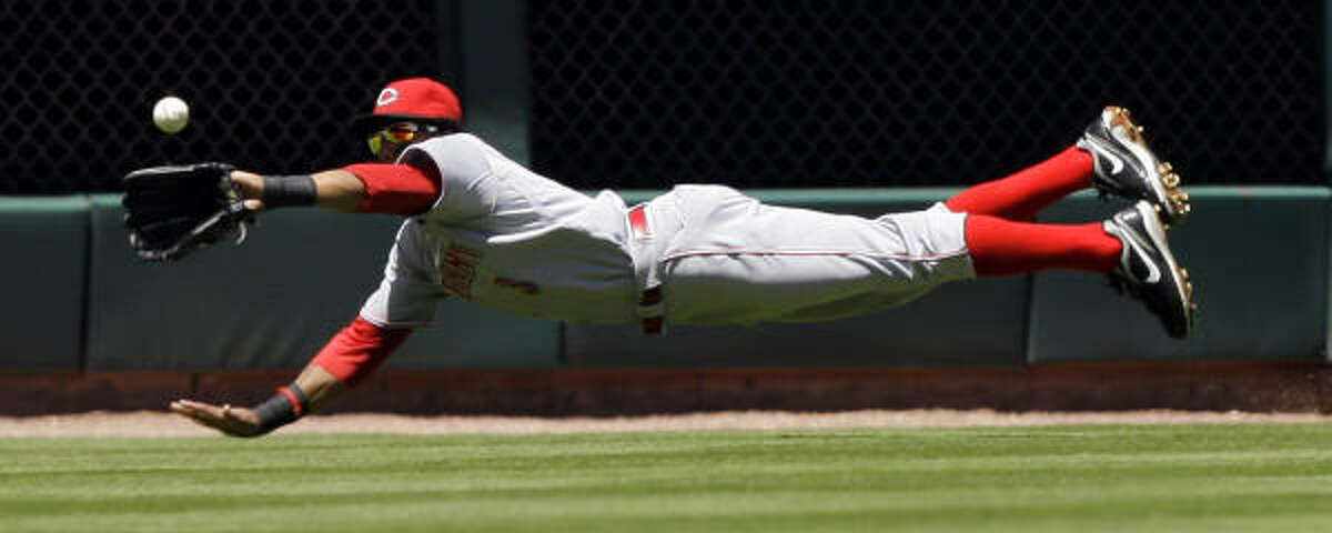 Cincinnati Reds center fielder Willy Taveras dives to catch a fly ball by Houston Astros' Michael Bourn during the first inning.