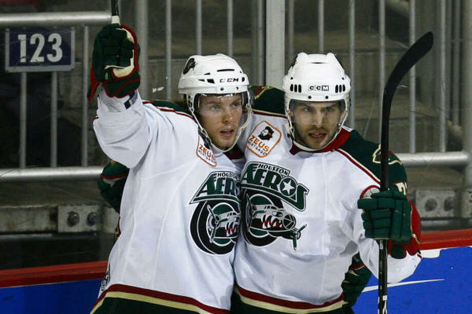 The Aeros' Corey Locke (left) celebrates his goal that put the Aeros up 1-0 during the second period of Game 3 against the Peoria Rivermen on Saturday at Toyota Center. The Aeros won 2-1 to take a 2-1 series lead. Photo: Michael Paulsen, Chronicle