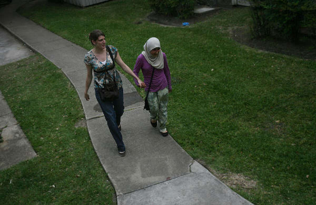 Army Capt. Liz Valette holds hands with Marzia Bostani, 11, as they walk to say good-bye to refugees from Afghanistan and Iraq in a southwest Houston apartment complex.