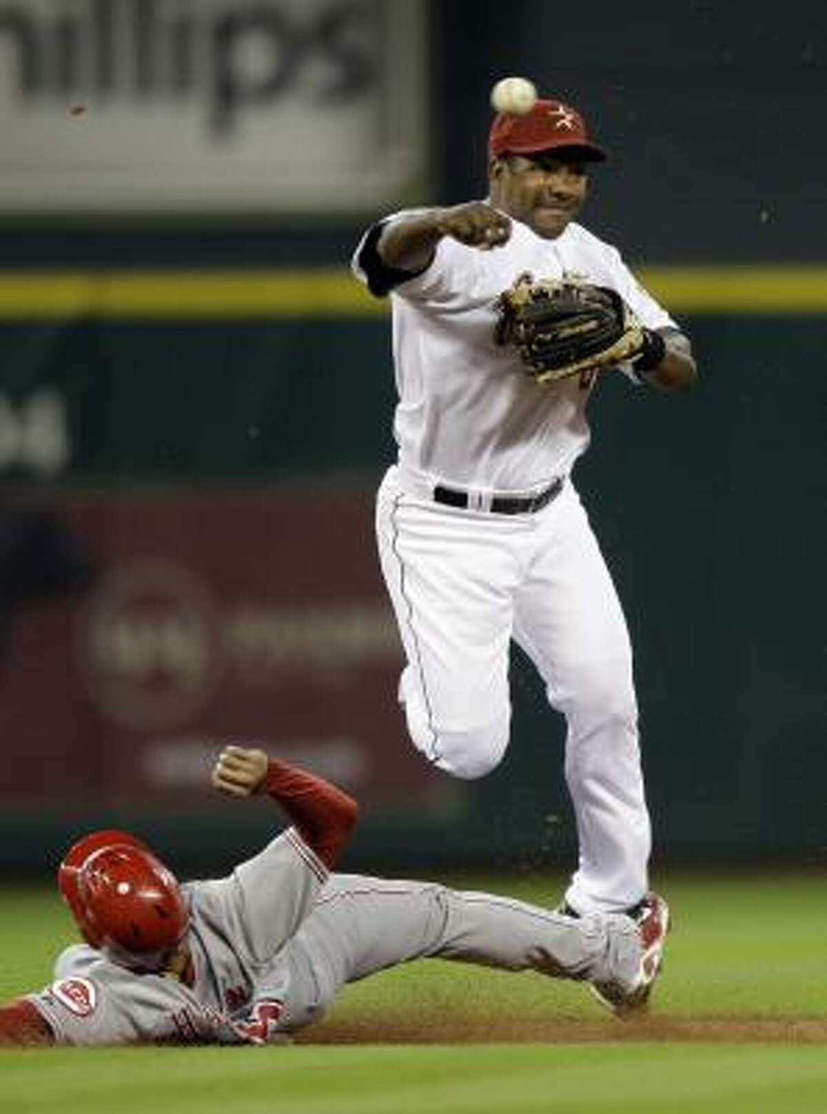 Astros shortstop Miguel Tejada throws to first base to complete a double play as Cincinnati Reds outfielder Jerry Hariston Jr. slides into second base during the first inning. Hariston Jr. was out at second and Joey Votto was out at first on the double play.