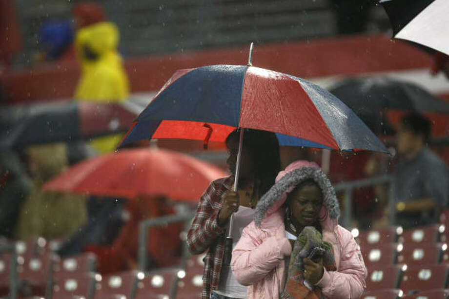 University of Houston football fans leaves the stands as the UH spring football game is called off because of lightning at Robertson Stadium. Photo: Brett Coomer, Chronicle