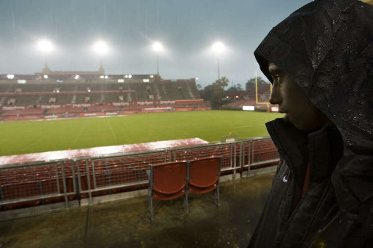 Dwayne Pearson stands in a tunnel watching the rain at Robertson Stadium during a rain delay at the UH spring football game. The game was called off shortly after it began due to lightning and severe weather that drenched the area.