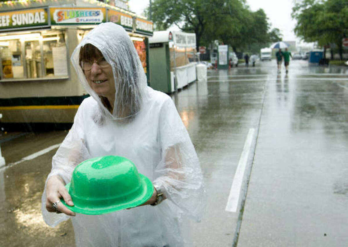 Linda Grasser covers her drink with a green plastic hat as she leaves iFest. The International Festival is set to resume Sunday under sunny skies.