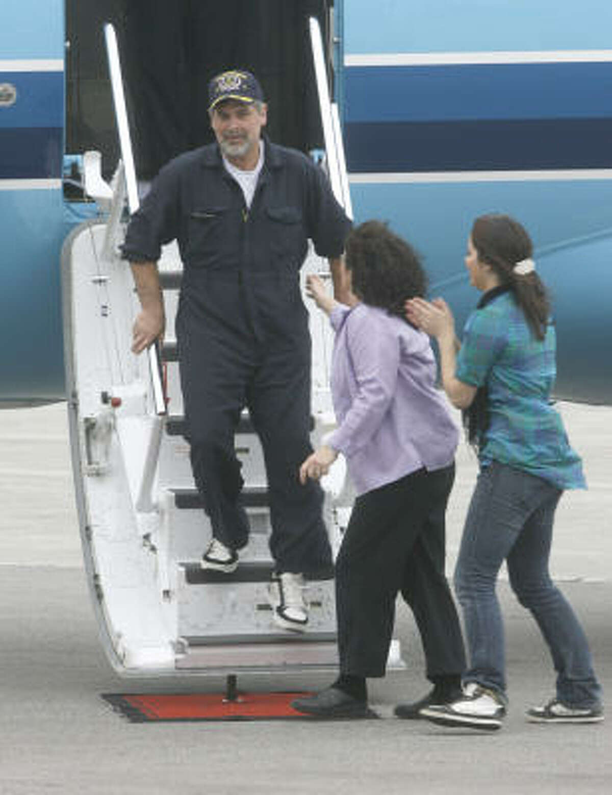 Phillips' wife, Andrea, center, and his daughter, Mariah, are among the first to welcome Phillips as he departs his plane in South Burlington, Vt.