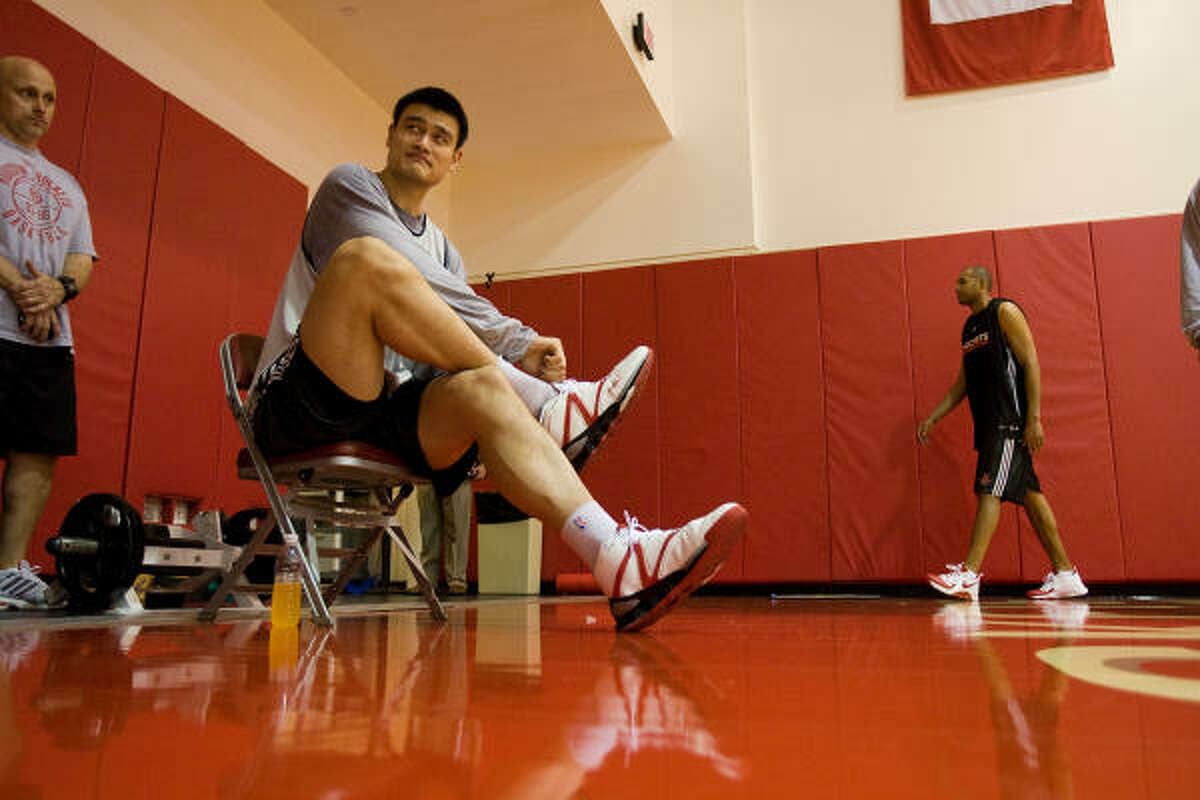 Rockets center Yao Ming takes his shoes off before taking to the media during practice.