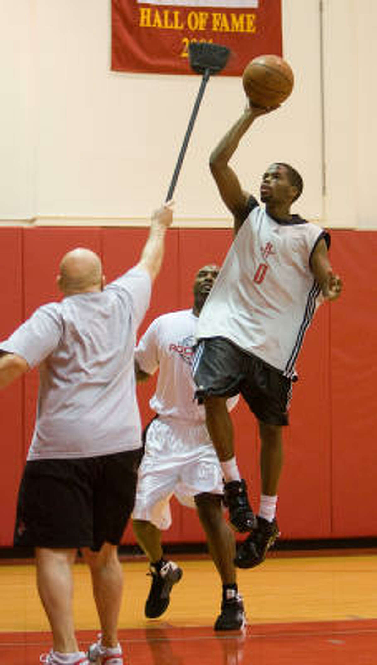 Rockets guard Aaron Brooks, center, works on his game with strength coaches and player development personnel during practice.