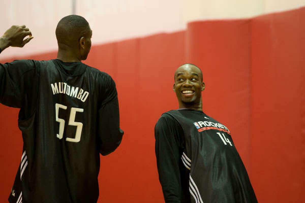 Rockets forward Carl Landry, facing, jokes with teammate Dikembe Mutombo during practice.