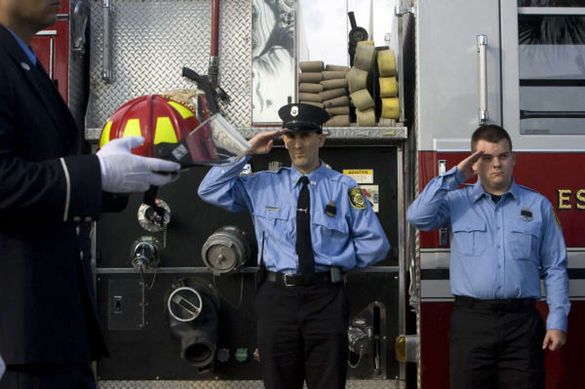 A firefighter carries the helmet of Capt. James Harlow during the procession.