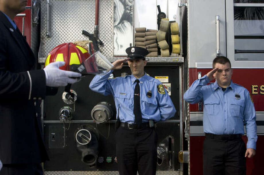 A firefighter carries the helmet of Capt. James Harlow during the procession. Photo: Johnny Hanson, Chronicle