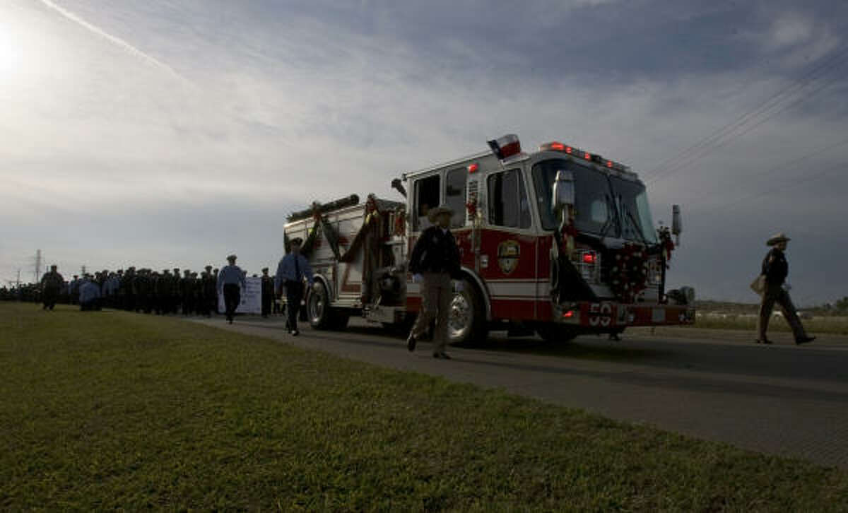 A fire truck carrying the casket of firefighter Damion Hobbs makes its way along the Gulf Freeway service road toward Grace Community Church.
