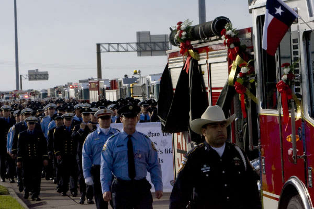 A fire truck carrying the casket of firefighter Damion Hobbs makes its way along the Gulf Freeway service road.