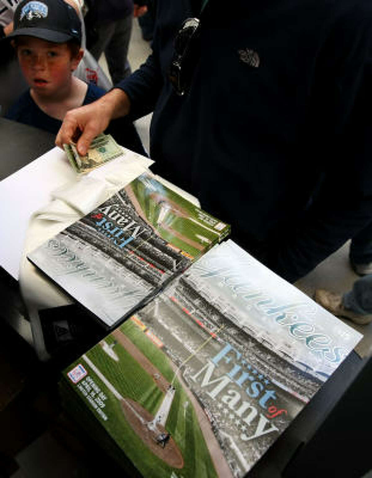 A fan buys a program before the game.