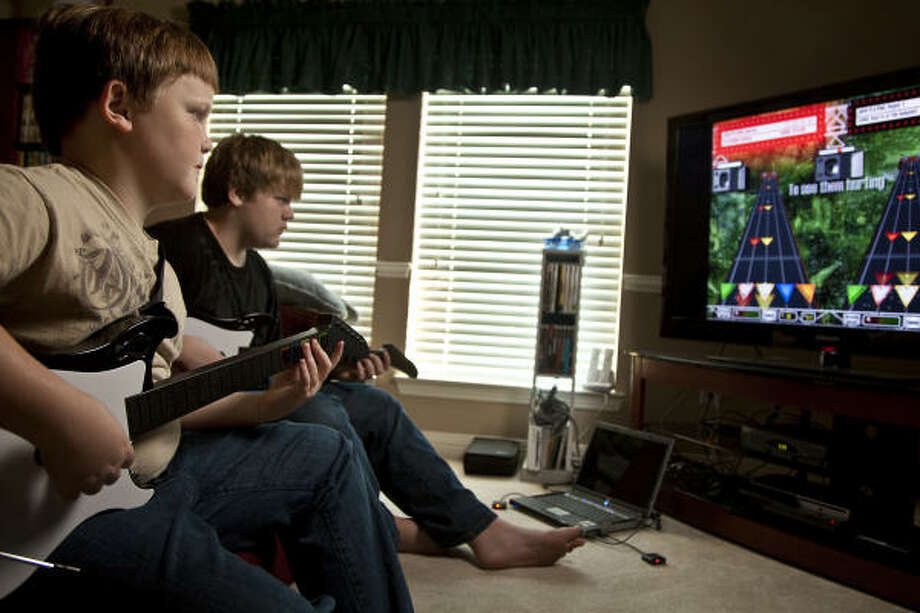 Andrew Sterling, 11, and his bother Stephen, 13, Friday play the video game Guitar Praise at their Clear Lake City home on March 20. Guitar Praise is a Christian-rock version of the popular game Guitar Hero. Photo: Smiley N. Pool, Houston Chronicle