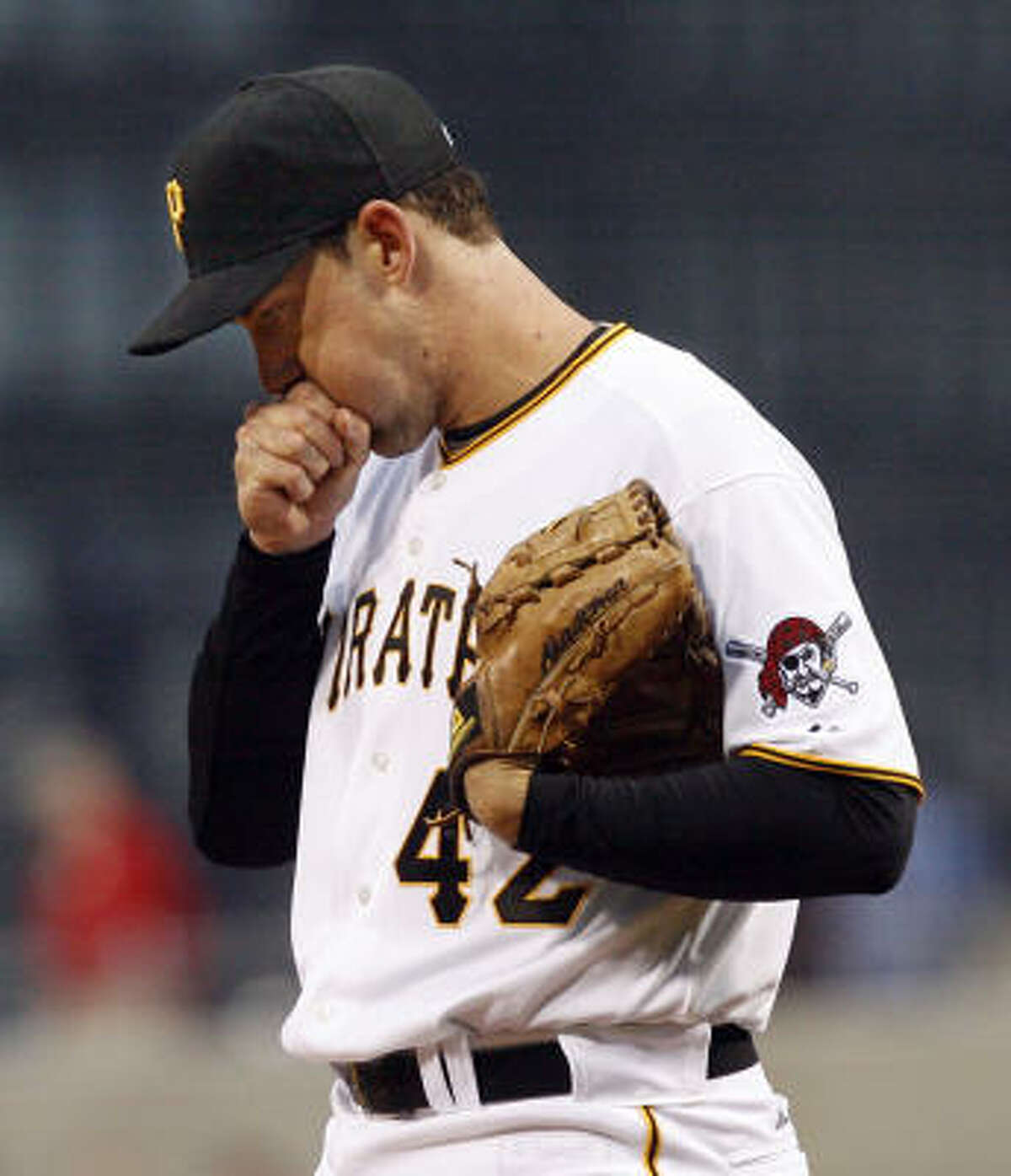 Pittsburgh Pirates starting pitcher Ross Ohlendorf blows on his hands after giving up two runs to the Houston Astros in the first inning.