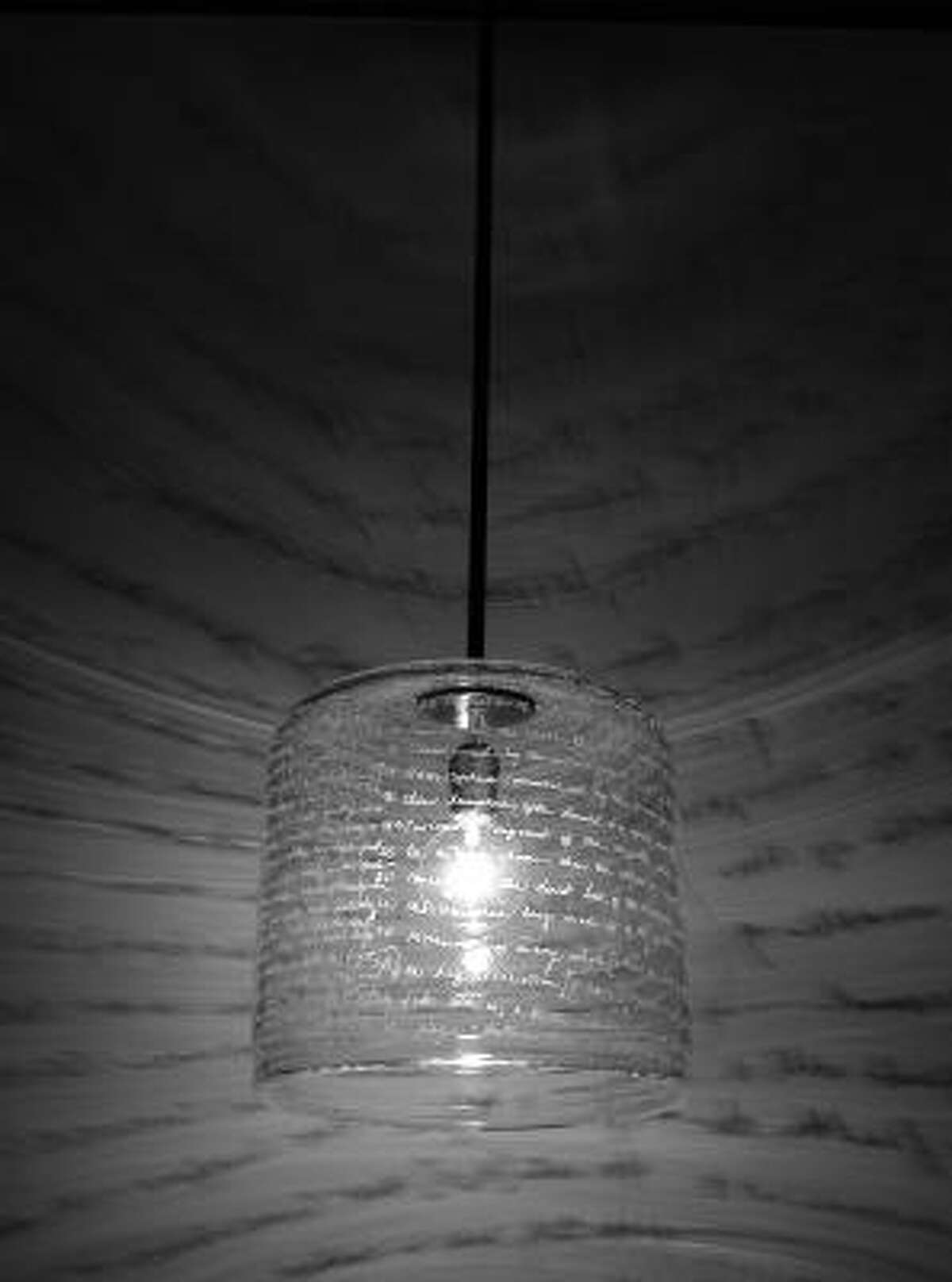 At night, the scrawlings on this hand-blown, crystal Word Pendant by Alison Berger are projected onto surrounding walls.