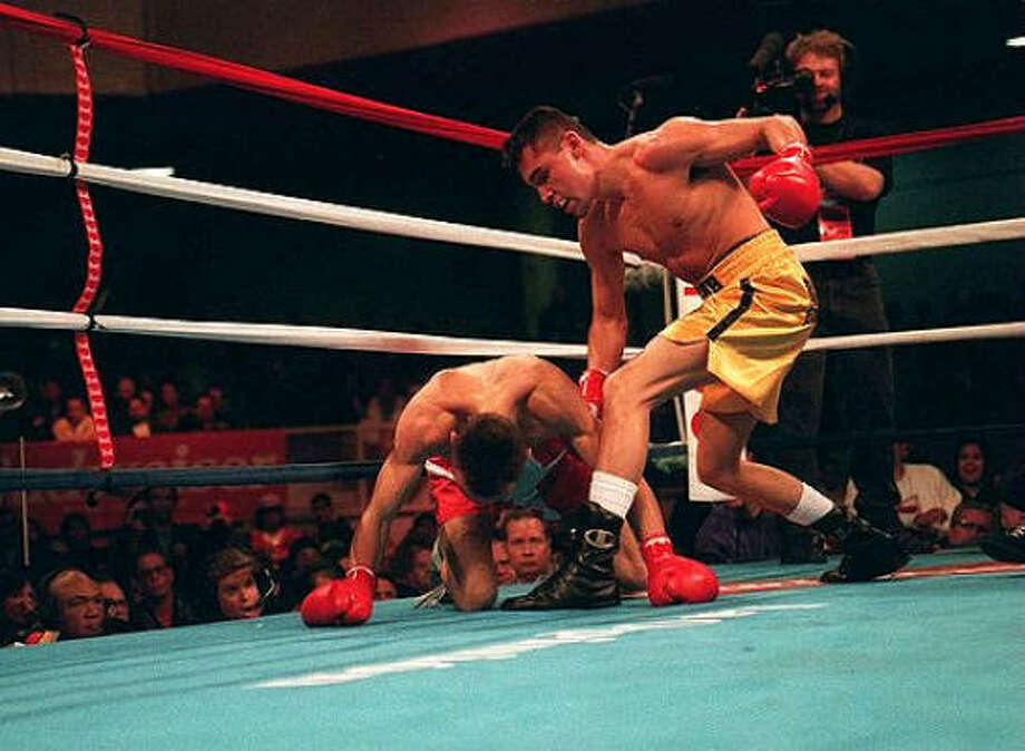 Oscar De La Hoya puts Jimmi Bredahl on the canvas as he won the WBO super-featherweight championship — his first world title — on March 5, 1994, at the Olympic Auditorium. Photo: Los Angeles Times