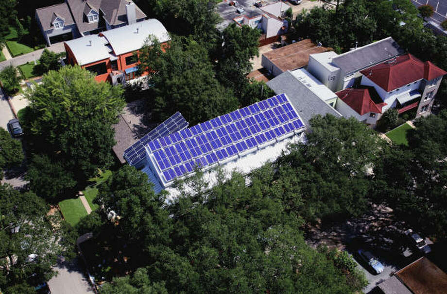 The roof of the Hedges home, fitted with 140 solar panels, rises above the tree line. Photo: Aker/Zvonkovic Photography