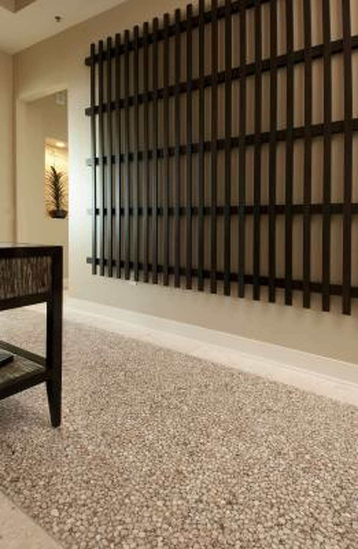 The entry features a dramatic grid of wood and a console table with painted, textured glass inserts from CR Currin.