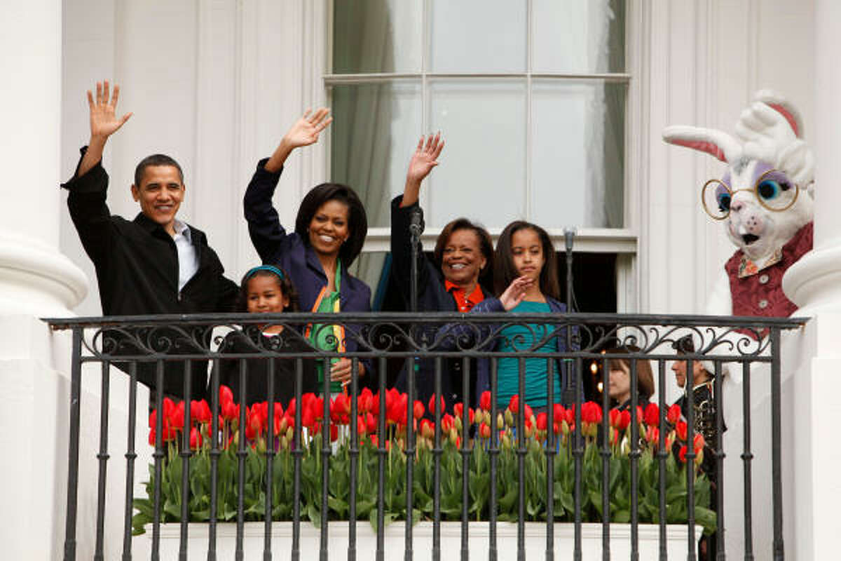 President Barack Obama and first lady Michelle Obama with daughters Malia, 10, and Sasha, 7, and their grandmother Marian Robinson, wave from the Truman Balcony at the start of the annual Easter Egg Roll at the White House.