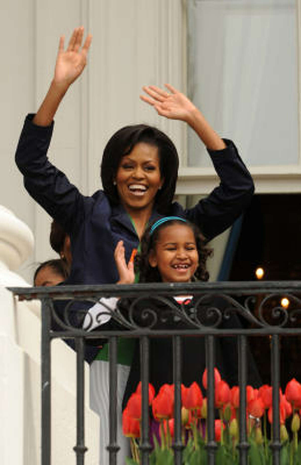 U.S. first lady Michelle Obama and her daughter Sasha Obama welcome people to the annual White House Easter Egg Roll on the South Lawn of the White House.