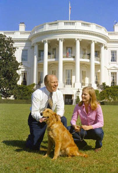 President Ford and his daughter Susan pose on the South Lawn with their golden retriever Liberty. On
