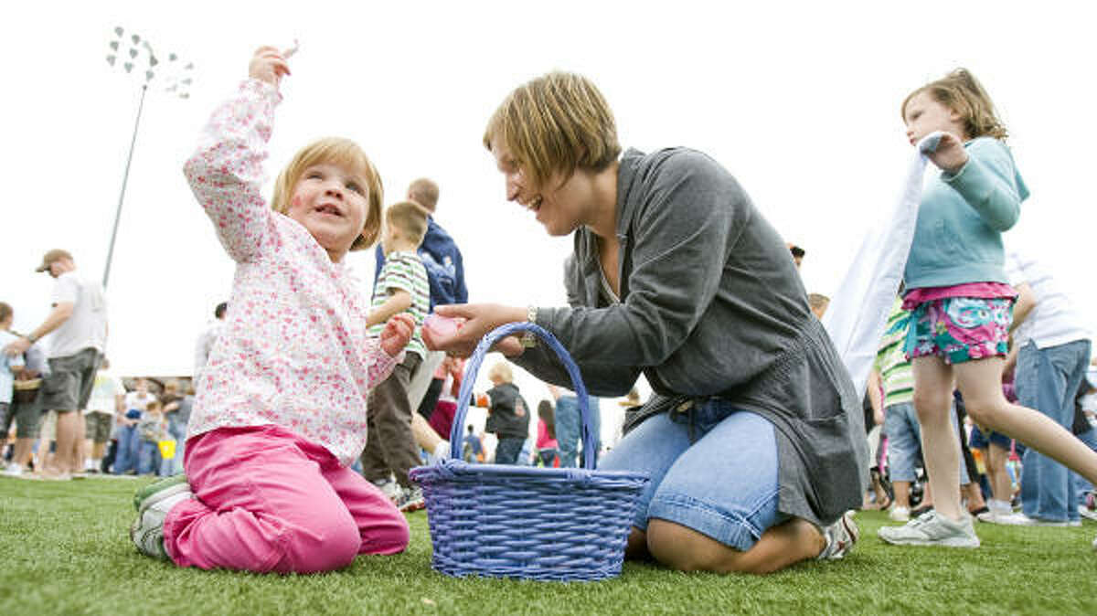 Jenna Branstetter, 3, of Pearland, is happy to get a piece of candy as she and her mother Melanie Branstetter look through the eggs they got during The Great Easter Egg Drop.