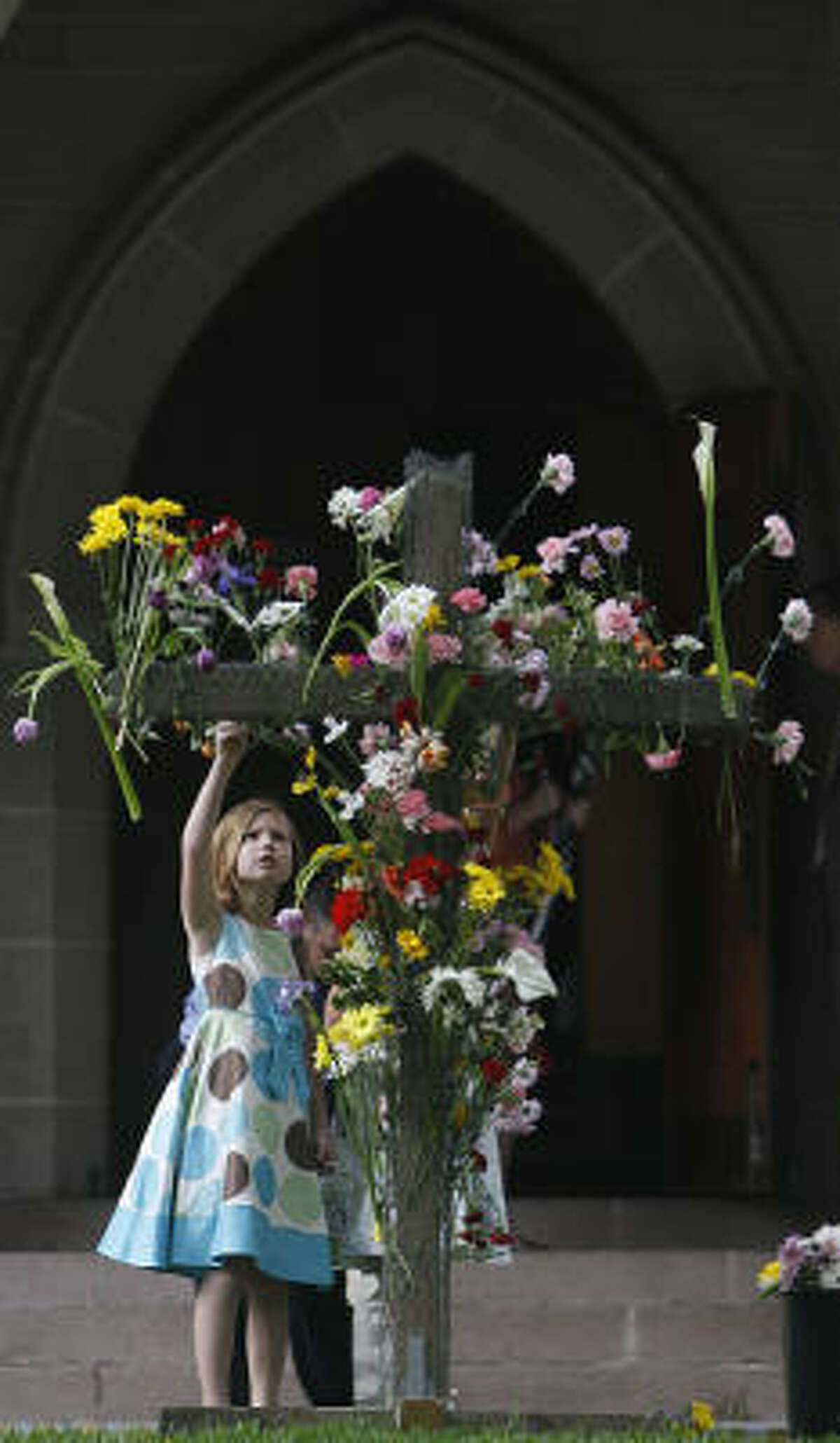 Emma Senpem places a flower on a wooden cross placed in the sanctuary lawn before attending Easter Service at St. Paul's United Methodist Church.