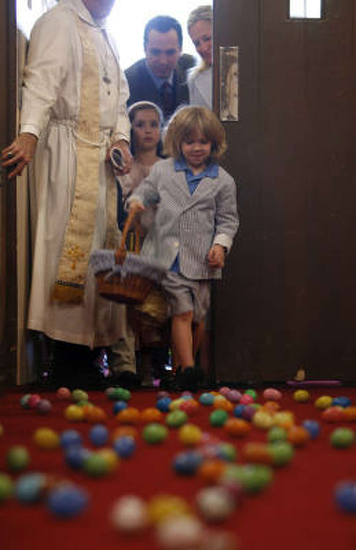 Lawson Schintler runs into the chapel for the Easter egg hunt after attending a service at The Church of St. John the Divine. The egg hunt was held indoors because of rainy weather.