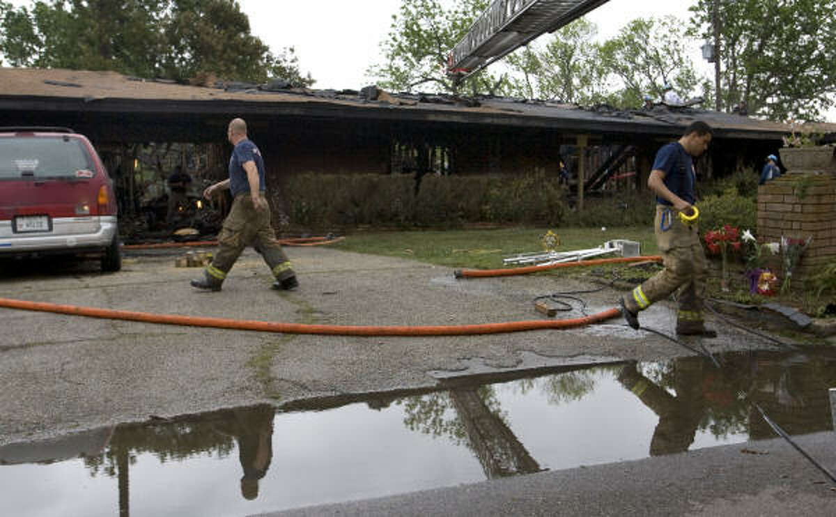 Houston firefighters work the scene where two fellow firefighters died fighting a one-alarm blaze early Sunday.