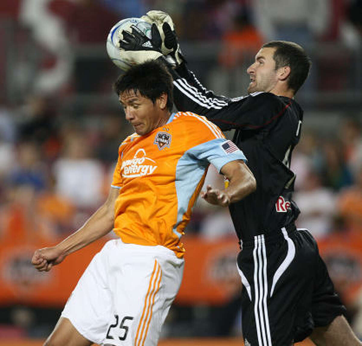 Dynamo forward Brian Ching goes up for a header as New York goalkeeper Alec Dufty makes a save during the second half.