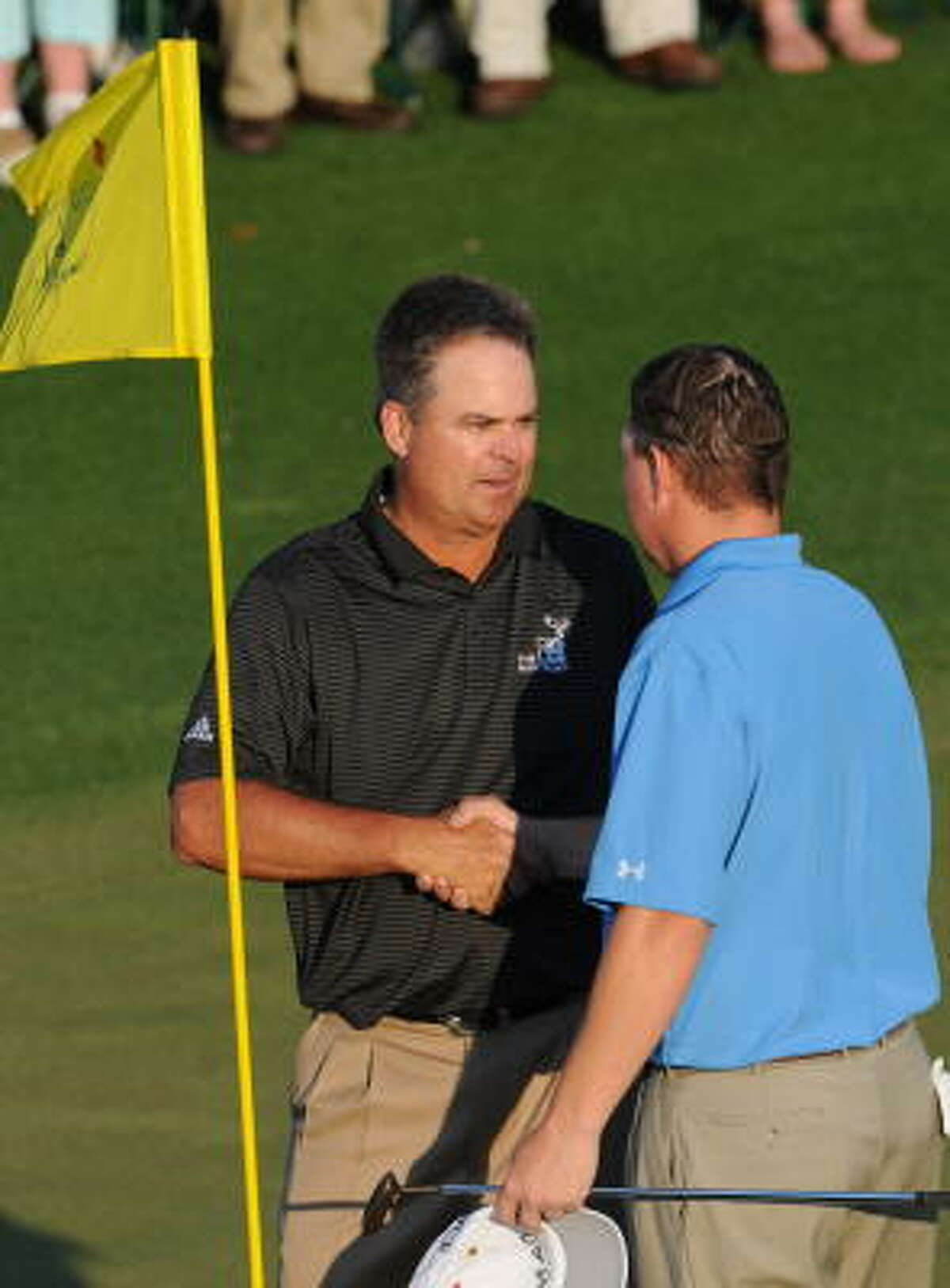 Kenny Perry (left) and Chad Campbell shake hands after completing the third round. Perry shares the lead with Argentinian Angel Cabrera at 11-under par.