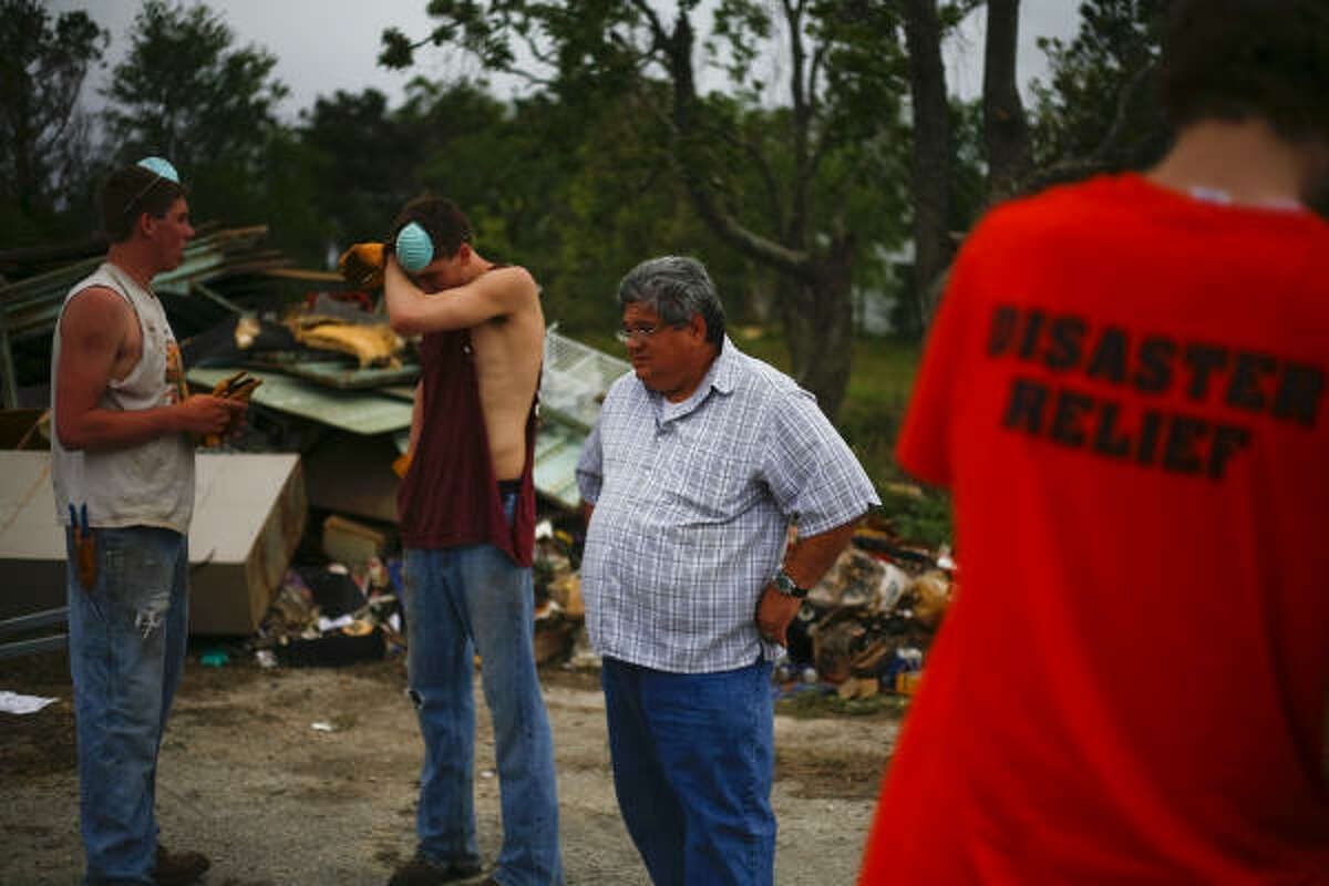 Pastor Eddie Shauberger watches the clean up efforts of those from Trinity Christian Reformed Church in Iowa who traveled to Texas over their spring break on a mission trip to help Shauberger and other members of the church clean up debris.