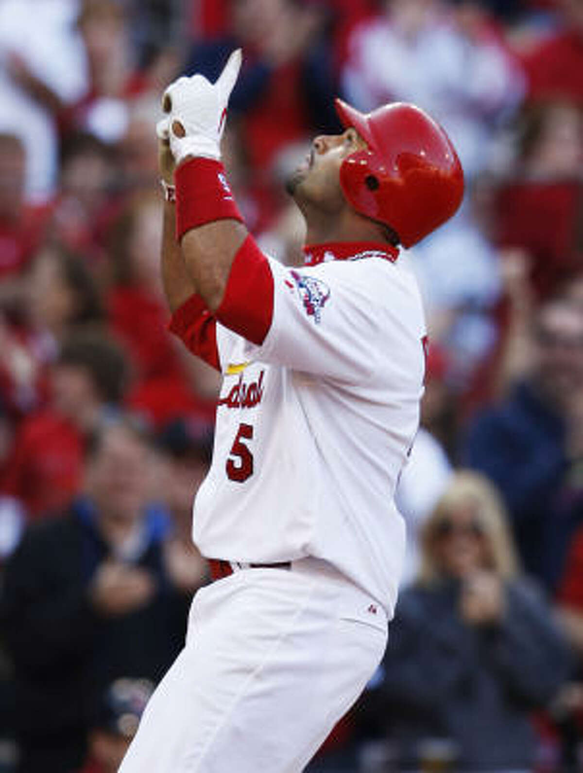 St. Louis Cardinals first baseman Albert Pujols points to the sky as he crosses home plate after hitting a three-run home run in the seventh inning.