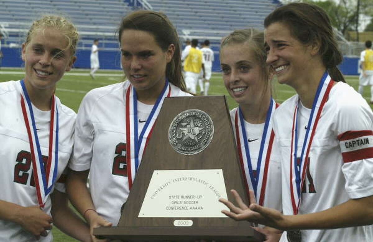 Some of The Woodlands players hold the second place trophy after the 3-2 loss to Coppell.