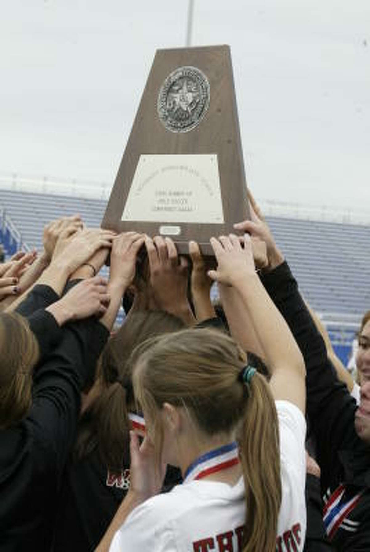 The Woodlands huddles and holds up the Class 5A second place trophy from the state tournament.