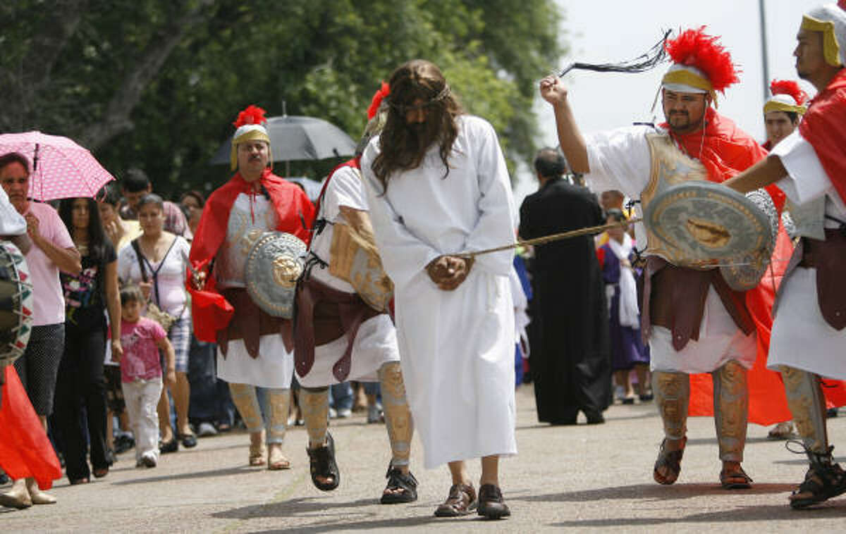 (Left to right) Pedro Corbera, portraying Jesus, is whipped by Roman soldiers Alonso Pedra during the dramatization of the Stations of the Cross for Holy Friday as the community has a procession through the El Dorado Neighborhood for the first time in the history of St. Phillip of Jesus Catholic Church.