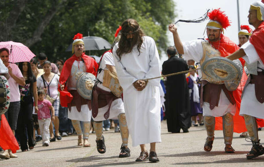 (Left to right) Pedro Corbera, portraying Jesus, is whipped by Roman soldiers Alonso Pedra during the dramatization of the Stations of the Cross for Holy Friday as the community has a procession through the El Dorado Neighborhood for the first time in the history of St. Phillip of Jesus Catholic Church. Photo: Mayra Beltran, Chronicle
