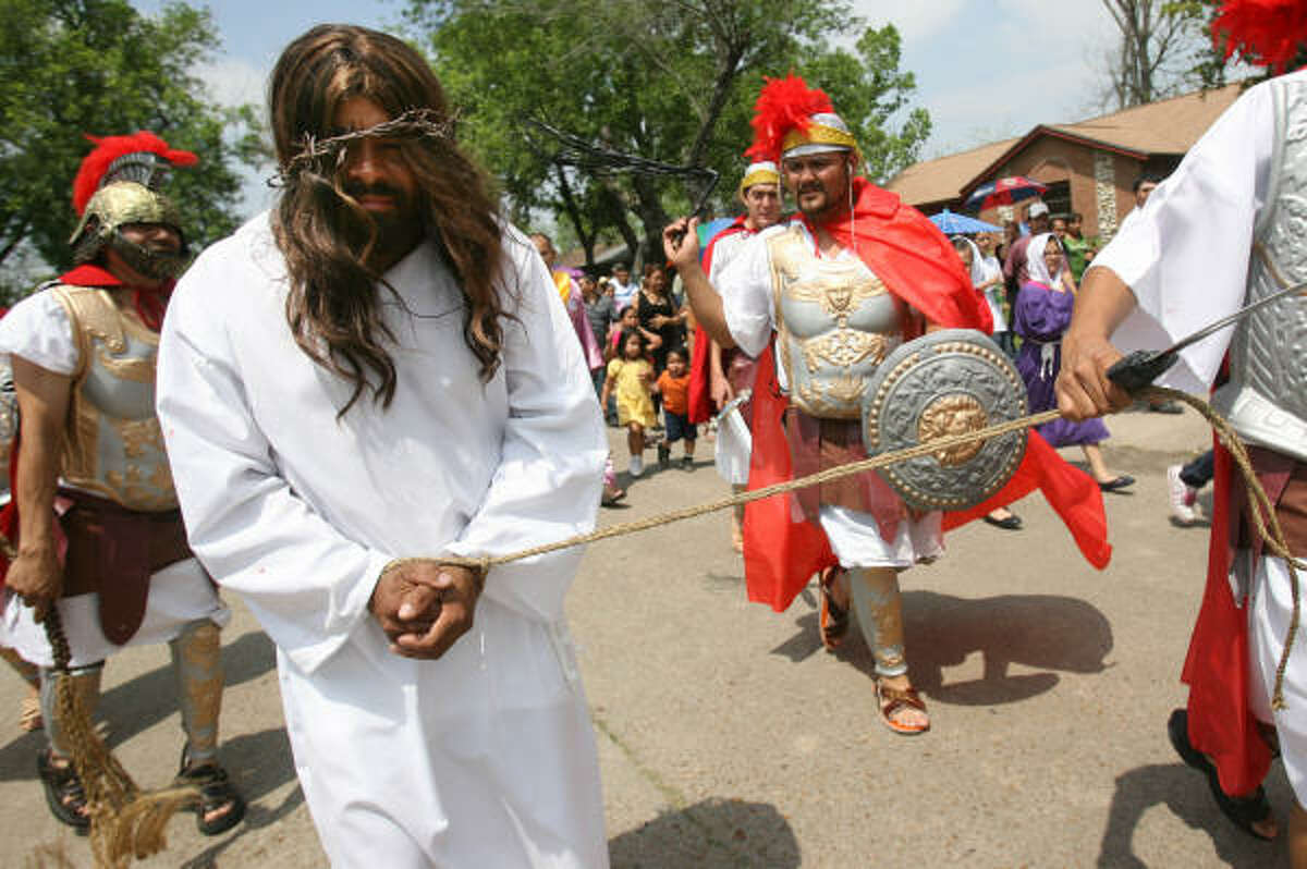 Pedro Corbera, portraying Jesus, is tied and whipped by Roman soldiers during the dramatization of the Stations of the Cross for Holy Friday as the community has a procession through the El Dorado Neighborhood for the first time in the history of St. Phillip of Jesus Catholic Church.