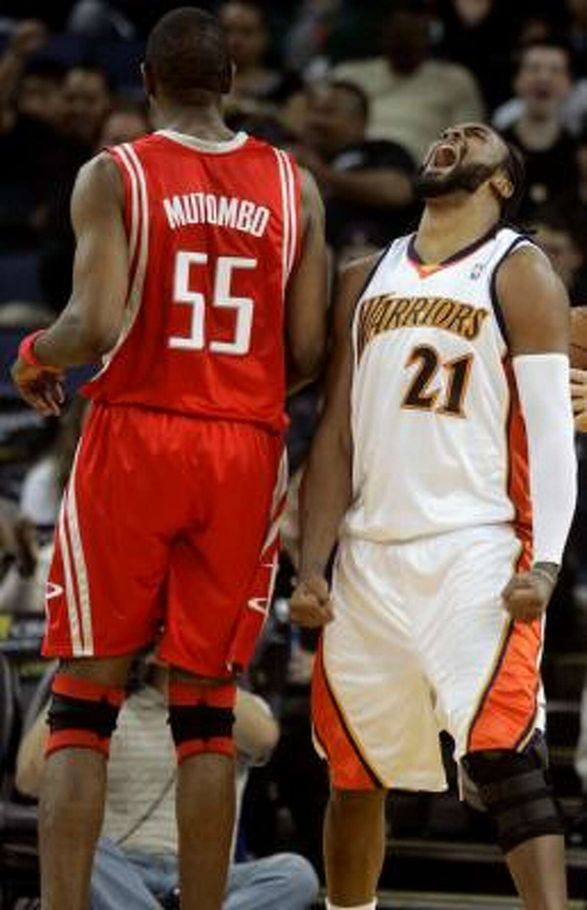 Golden State Warriors forward Ronny Turiaf (21) yells after making a basket next to Rockets center Dikembe Mutombo (55) in the third quarter.