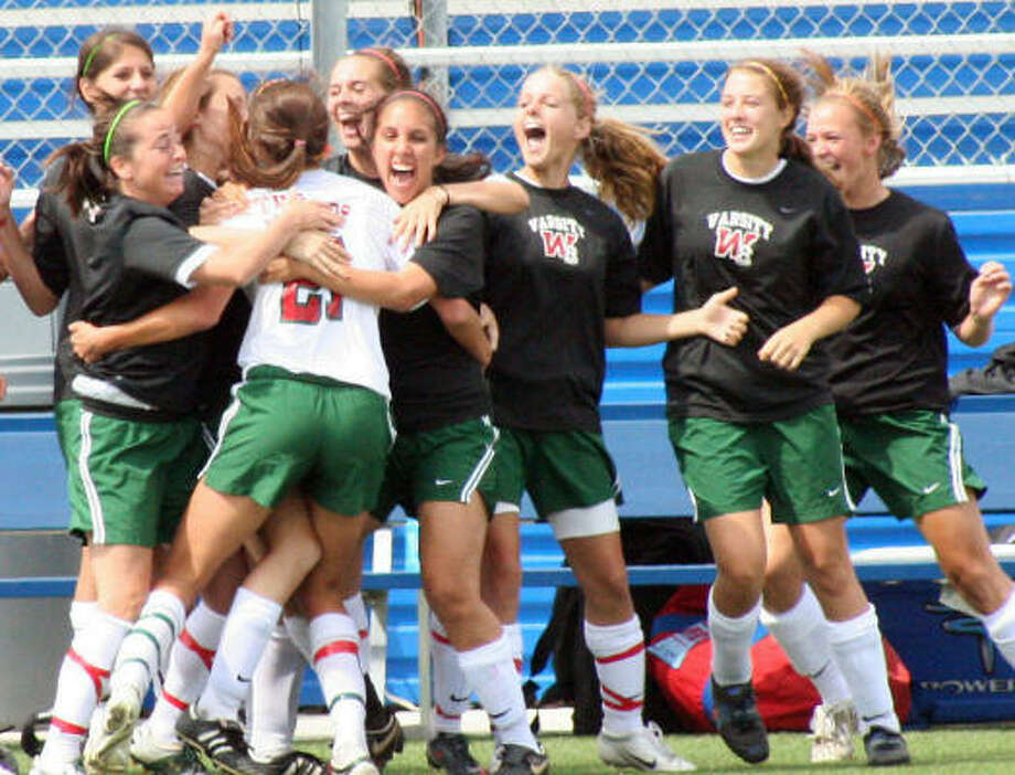 The Woodlands' Kylie Cook celebrates with teammates after she scored the first goal of the match Friday. Photo: Gerald James, Chronicle