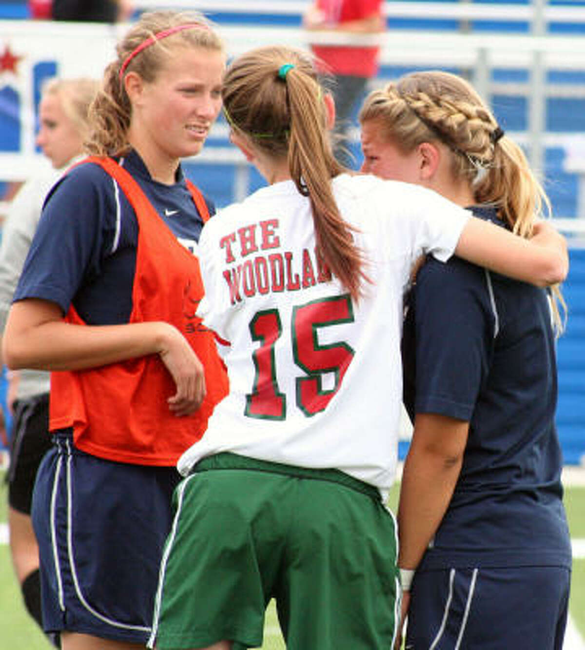 The Woodland's Kelsey Missimer consoles opponent Ana Pontes after the game.