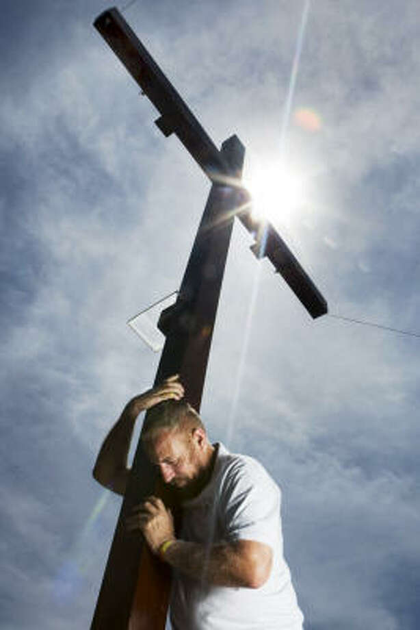 "Joe Gaston poses for a portrait with the cross he will hang on to commemorate Christ's crucifixion.  ""When I put my Jesus outfit on and go up there (on the cross), it's indescribable,"" said Gaston, who has done his crucifixion re-enactment for five years now. I like to see the reactions of the people and how they are touched."" Gaston will place himself on the cross starting Friday at 7 a.m. to 6 p.m. and again on Saturday for the same hours at the intersection of Allendale and Howard. Photo: Brett Coomer, Chronicle"