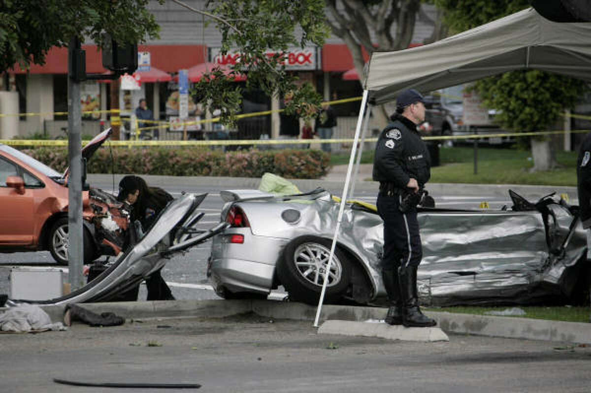 Fullerton, Calif., police officers work the scene where a driver ran a light and struck Nick Adenhart's sports car.