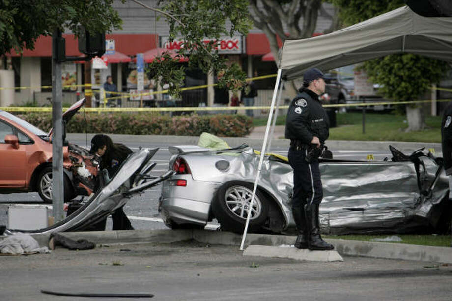 Fullerton, Calif., police officers work the scene where a driver ran a light and struck Nick Adenhart's sports car. Photo: Nick Ut, AP