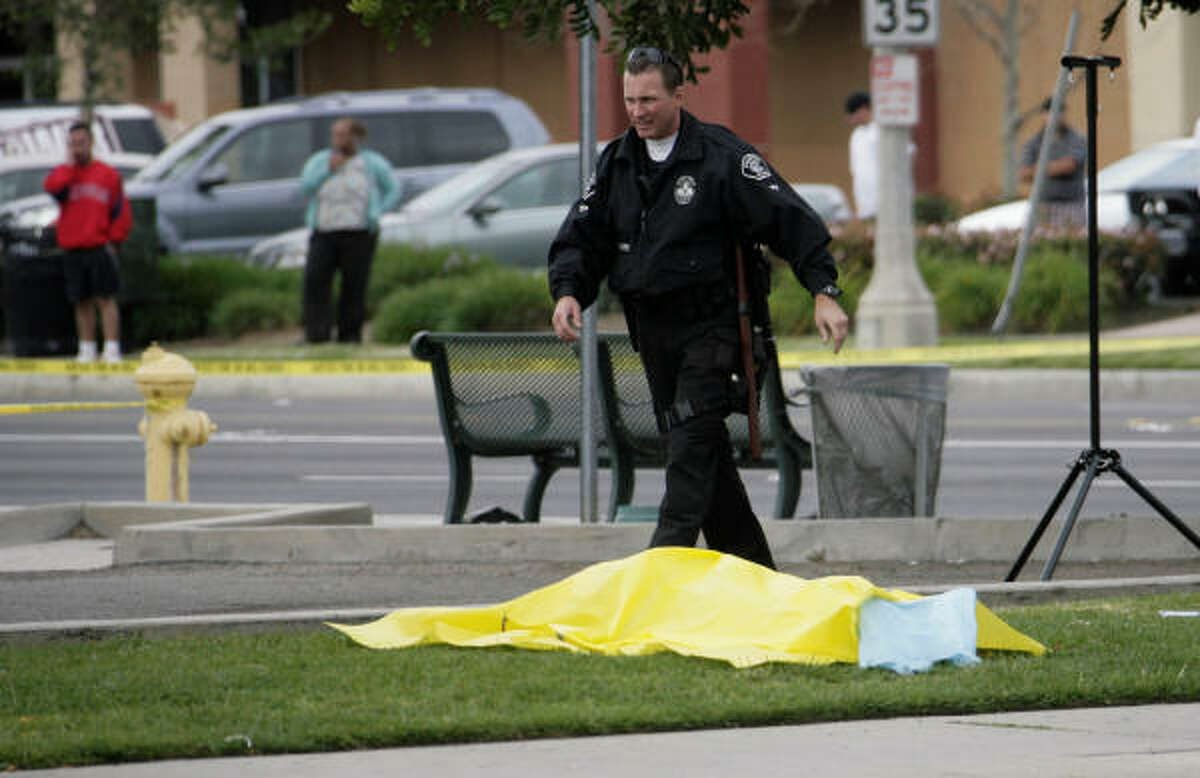 A victim is covered by a sheet as police work the scene.
