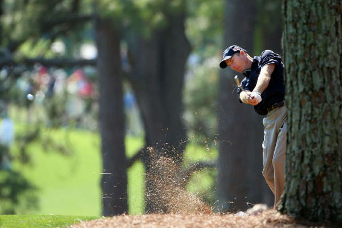 Jim Furyk hits a shot from the pine straw on the first hole.
