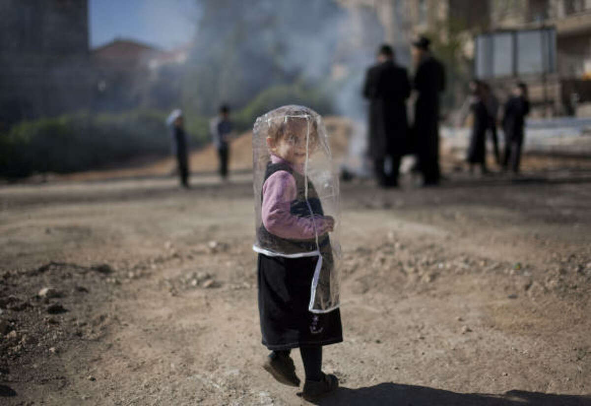 An Ultra-Orthodox Jewish girl wears a plastic cover to protect her from the smoke as others burn leavened items in a final preparation before the Passover holiday, in Jerusalem, Wednesday, April 8, 2009.